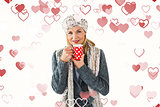 Composite image of smiling woman in winter fashion looking at camera with mug