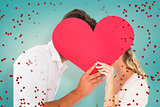 Composite image of attractive young couple kissing behind large heart