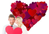 Composite image of attractive young couple holding red heart