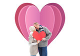 Composite image of happy mature couple in winter clothes holding red heart