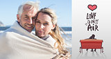 Composite image of smiling couple wrapped up in blanket on the beach