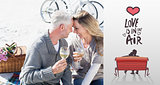 Composite image of couple enjoying white wine on picnic at the beach smiling at each other