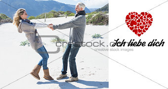 Composite image of smiling couple spinning on the beach in warm clothing