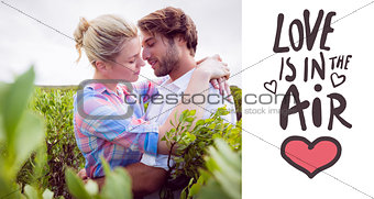 Composite image of smiling couple embracing outside among the bushes