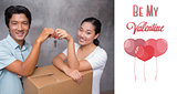 Composite image of happy couple holding house key and leaning on moving box