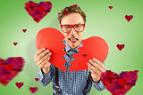 Composite image of geeky hipster holding a broken heart