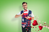 Composite image of geeky hipster offering christmas gift