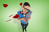 Composite image of geeky hipster looking at camera holding keyboard
