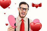 Composite image of geeky hipster crying and holding broken heart card