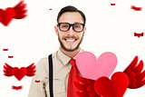 Composite image of geeky hipster smiling and holding heart card