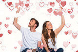 Composite image of happy young couple with hands raised