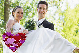 Composite image of groom carrying bride in garden