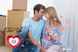 Composite image of couple holding new house key against cardboard boxes