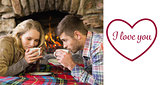 Composite image of romantic couple drinking tea in front of lit fireplace