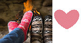 Composite image of close up of romantic legs in socks in front of fireplace