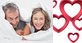 Composite image of happy middle aged couple under the duvet