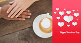 Composite image of couple holding hands beside cappuccino