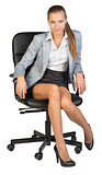 Businesswoman sitting on office chair, looking at camera