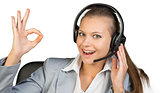 Businesswoman in headset making okay gesture
