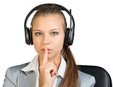 Businesswoman in headset holding finger to her lips