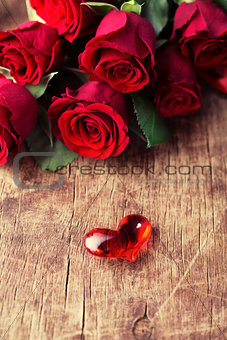 Small glass heart on wooden background