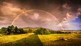 Double Rainbow over Landscape at Sunset