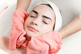 Young woman facial treatment or massage with towel