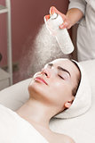 serum mask spraying from can on young woman's face in spa salon