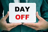 businessman with a signboard with the text day off