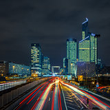 Night road with skyscrapers of La Defense, Paris, France.