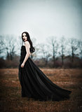 Beautiful sad goth girl stands in autumnal field. Grunge texture