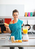 Portrait of happy fitness young woman making pumpkin smoothie in