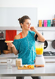 Happy fitness young woman making pumpkin smoothie in kitchen and