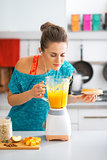 Fitness young woman making pumpkin smoothie in kitchen