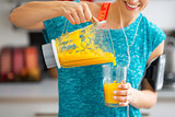 Close-up on fitness young woman pouring pumpkin smoothie in glas