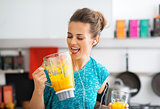 Fitness young woman with pumpkin smoothie in kitchen