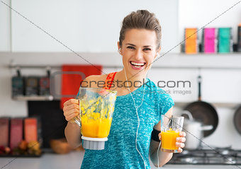 Portrait of happy fitness young woman with pumpkin smoothie in k
