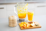 Close-up on pumpkin smoothie and ingredients on table in kitchen