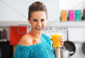 Portrait of smiling fitness young woman with glass of pumpkin sm
