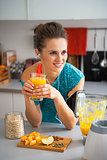 Happy fitness young woman with pumpkin smoothie in modern kitche