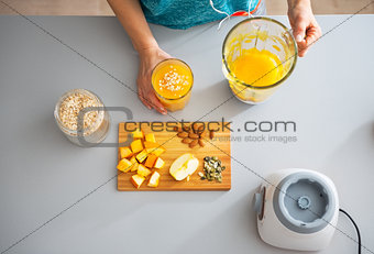 Fitness young woman making pumpkin smoothie