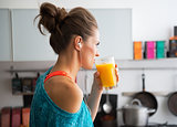 Fitness young woman drinking pumpkin smoothie in kitchen