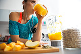 Close-up on fitness young woman drinking pumpkin smoothie in kit