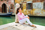 Young woman sitting on street in venice, italy