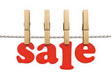 Red sale text with wooden clothespins on the clothesline