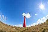 sun shining over red lighthouse