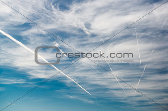 Blue sky with clouds and trails of airplanes