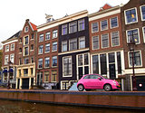 pink car on a canal in Amsterdam, Netherlands