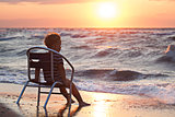 Little child looking at sunset sitting by the sea