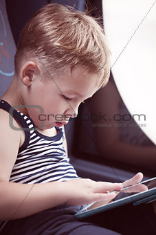 Little child using touch pad while traveling by bus